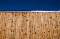 Image of a wooden fence shot from a low angle looking slightly up with blue sky Stock Photo - Royalty-Freenull, Code: 400-05322119