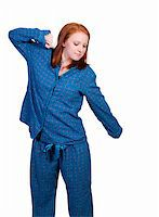 A young stretching woman waking up in her pajamas in the morning Stock Photo - Royalty-Freenull, Code: 400-05331884
