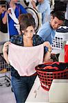 Worried young lady holds oversize granny panties in laundromat Stock Photo - Royalty-Free, Artist: creatista                     , Code: 400-05347593