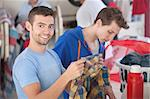 Smiling Caucasian man holds plaid shirt in laundromat Stock Photo - Royalty-Free, Artist: creatista                     , Code: 400-05347599