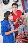 Latino and Caucasian men can't explain clothing switch in laundromat Stock Photo - Royalty-Free, Artist: creatista                     , Code: 400-05347607