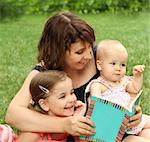 Mother and children reading a book in summer park Stock Photo - Royalty-Free, Artist: DashaPetrenko                 , Code: 400-05359458