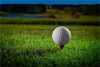 Image of a beautifully lit golf ball on a red tee with course in background Stock Photo - Royalty-Freenull, Code: 400-05372599