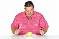 Fat man eating a apple isolated on white background Stock Photo - Royalty-Freenull, Code: 400-05376850