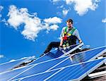 Worker installing alternative energy photovoltaic solar panels on roof Stock Photo - Royalty-Free, Artist: Elenathewise                  , Code: 400-05380326