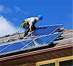 Man installing alternative energy photovoltaic solar panels on roof Stock Photo - Royalty-Free, Artist: Elenathewise                  , Code: 400-05386112