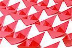 Several red paper boats on white background