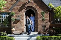 Smiling Mother stands at front door of house as son departs Stock Photo - Premium Royalty-Freenull, Code: 653-05393270