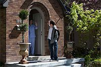 Son and Mother waving goodbye to each other at their front door as son leaves house Stock Photo - Premium Royalty-Freenull, Code: 653-05393273