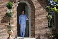 Smiling woman wearing Pajamas leans on front door and looks out Stock Photo - Premium Royalty-Freenull, Code: 653-05393275