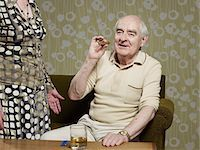 Senior man sitting on couch smoking cigar Stock Photo - Premium Royalty-Freenull, Code: 653-05393358