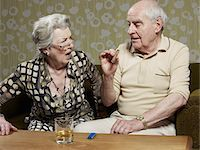 Senior woman looks shocked as senior man smokes cigar Stock Photo - Premium Royalty-Freenull, Code: 653-05393366