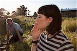 Girl smoking in field as guy in background watches Stock Photo - Premium Royalty-Free, Artist: Aurora Photos            , Code: 653-05393458