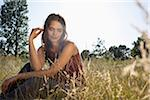 Girl sitting amongst timothy grass touching her hair Stock Photo - Premium Royalty-Free, Artist: Aurora Photos            , Code: 653-05393494