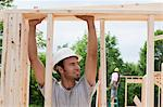 Carpenter lifting a board on framing Stock Photo - Premium Royalty-Freenull, Code: 6105-05396016