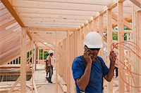 phone cord - Carpenter holding power cord and talking on mobile phone Stock Photo - Premium Royalty-Freenull, Code: 6105-05396077