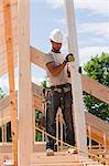 Carpenter holding a roof rafter Stock Photo - Premium Royalty-Free, Artist: Glowimages, Code: 6105-05396109