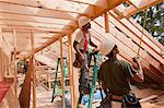 Hispanic carpenters using tape measure at a house under construction Stock Photo - Premium Royalty-Freenull, Code: 6105-05396154