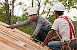 Hispanic carpenters working with a nail gun on the roof of a under construction house Stock Photo - Premium Royalty-Freenull, Code: 6105-05396190