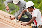 Hispanic carpenters using hammers on the roof of an under construction house Stock Photo - Premium Royalty-Freenull, Code: 6105-05396193