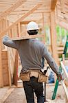 Hispanic carpenter carrying a board on the upper floor at a house under construction Stock Photo - Premium Royalty-Freenull, Code: 6105-05396199