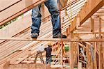 Hispanic carpenters pulling up air hose while standing on support board at a house under construction Stock Photo - Premium Royalty-Freenull, Code: 6105-05396211