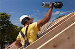 Hispanic carpenter using nail gun on roofing at a house under construction Stock Photo - Premium Royalty-Freenull, Code: 6105-05396244