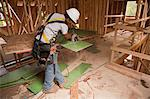Carpenter using a circular saw on exterior wall sheathing in a house under construction Stock Photo - Premium Royalty-Freenull, Code: 6105-05396283