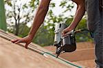 Hispanic carpenter using a nail gun on the roof panel of a house under construction Stock Photo - Premium Royalty-Freenull, Code: 6105-05396301