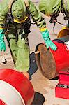 HazMat firefighters plugging a drum Stock Photo - Premium Royalty-Free, Artist: Ikon Images, Code: 6105-05396502