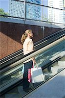 Woman carrying shopping bags going up on escalator outdoors Stock Photo - Premium Royalty-Freenull, Code: 632-05401017
