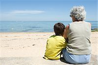 Grandmother and grandson sitting together on beach, looking at sea Stock Photo - Premium Royalty-Freenull, Code: 632-05401151