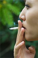 Young woman smoking outdoors, side view Stock Photo - Premium Royalty-Freenull, Code: 633-05401567