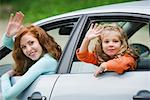 Mother and young daughter leaning out of car windows, waving Stock Photo - Premium Royalty-Free, Artist: Blend Images, Code: 633-05401599