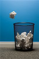 Crumpled paper about to fall into waste basket Stock Photo - Premium Royalty-Freenull, Code: 6106-05402647