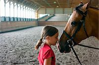 preteen kissing - Girl nose to nose with horse in riding arena. Stock Photo - Premium Royalty-Freenull, Code: 6106-05402790