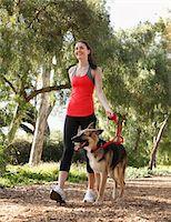 Girl walking dog on tree lined path Stock Photo - Premium Royalty-Freenull, Code: 6106-05405436