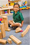 Preschool sitting among wooden blocks in classroom Stock Photo - Premium Royalty-Free, Artist: Rolf Bruderer, Code: 6106-05408870