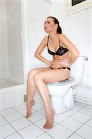 Young woman sitting on a toilet holding stomach Stock Photo - Premium Royalty-Freenull, Code: 6106-05410318