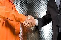 Businessman and manual worker shaking hands Stock Photo - Premium Royalty-Freenull, Code: 6106-05413294