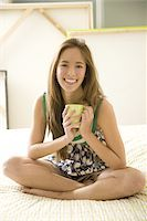 girl sitting on bed with coffee cup Stock Photo - Premium Royalty-Freenull, Code: 6106-05418843