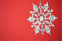 snowflakes  holiday - Snowflake Christmas ornament on red background Stock Photo - Premium Royalty-Freenull, Code: 6106-05432429