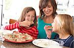 Mom and two girls eating christmas cake Stock Photo - Premium Royalty-Free, Artist: Aurora Photos, Code: 6106-05442469