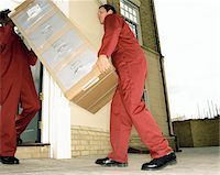 Two delivery men carrying filing cabinet, low angle view Stock Photo - Premium Royalty-Freenull, Code: 6106-05452524
