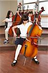 Three schoolgirls (6-12) playing cellos in music room Stock Photo - Premium Royalty-Free, Artist: Blend Images             , Code: 6106-05452588