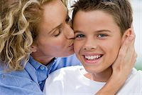 Boy (13-15) being kissed by mother, smiling, portrait Stock Photo - Premium Royalty-Freenull, Code: 6106-05452752