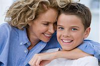 Boy (13-15) being embraced by mother, smiling, portrait Stock Photo - Premium Royalty-Freenull, Code: 6106-05452753