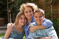 Mother hugging son and daughter (13-15) in garden, smiling, portrait Stock Photo - Premium Royalty-Freenull, Code: 6106-05452769
