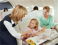 Mother and child smiling at female air stewardess on plane Stock Photo - Premium Royalty-Freenull, Code: 6106-05452814