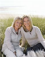 Mother and mature daughter sitting on grass, smiling, portrait Stock Photo - Premium Royalty-Freenull, Code: 6106-05452958